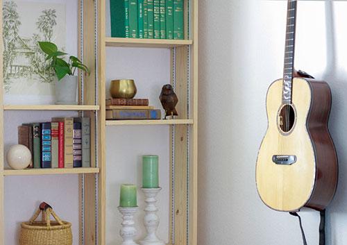 denver staging design of guitar hung on wall next to bookshelf