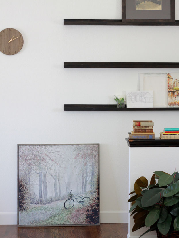 artsy floating bookshelf with clean hardwood floors and painting placed on floor