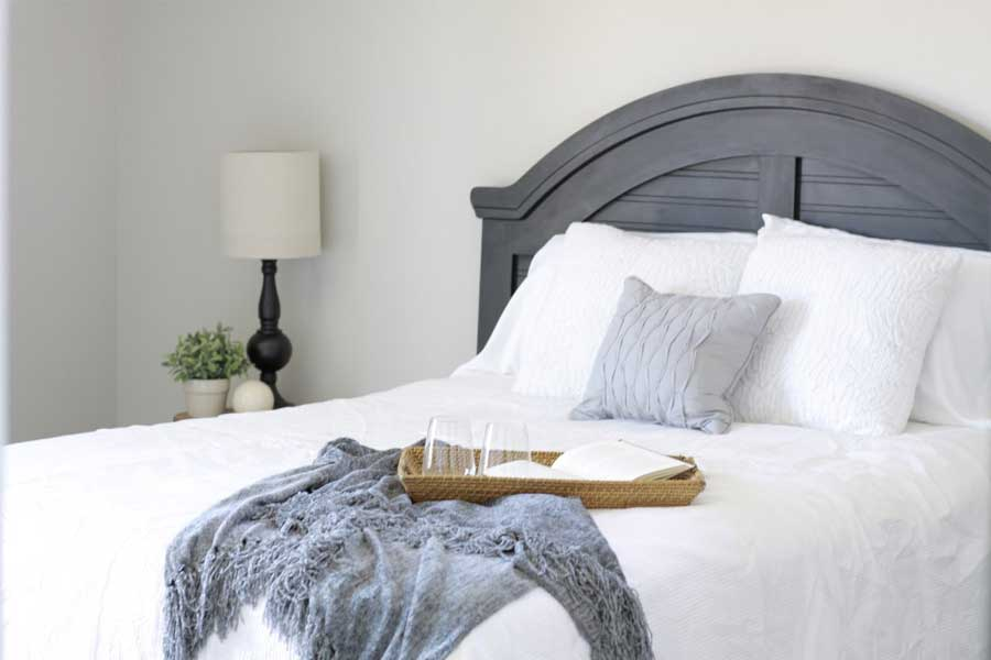 completed home staging consultation in bedroom with white covers and gray blanket