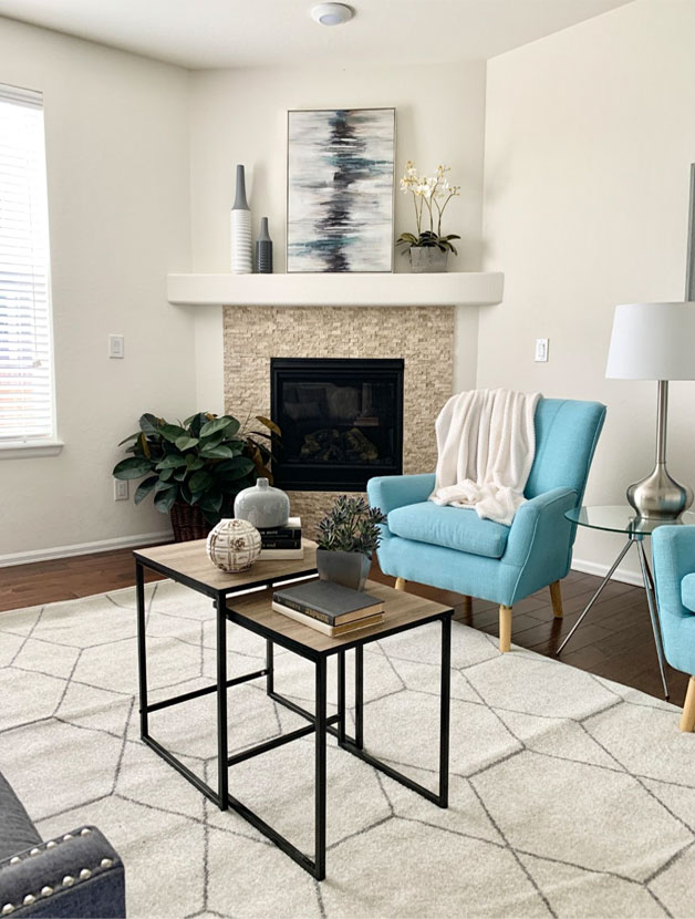 artistic living room with blue furniture and large painting on the mantle
