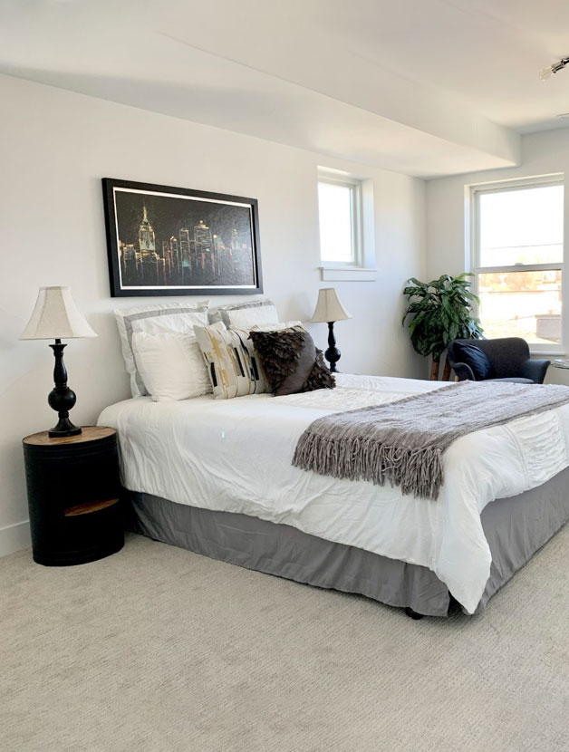 quaint bright bedroom with grey and white bedding